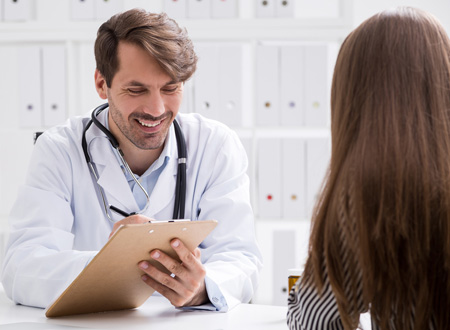 doctor with clipboard smiling and taking down patient's information